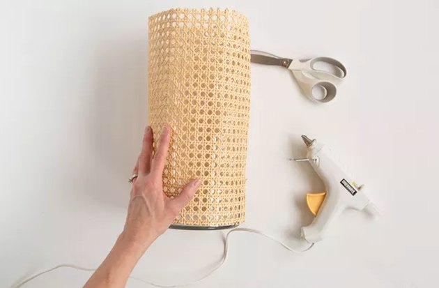 Wrapping cane around a vase with glue gun and scissors