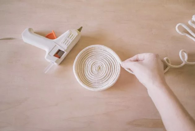 hand making bowl using rope and glue gun