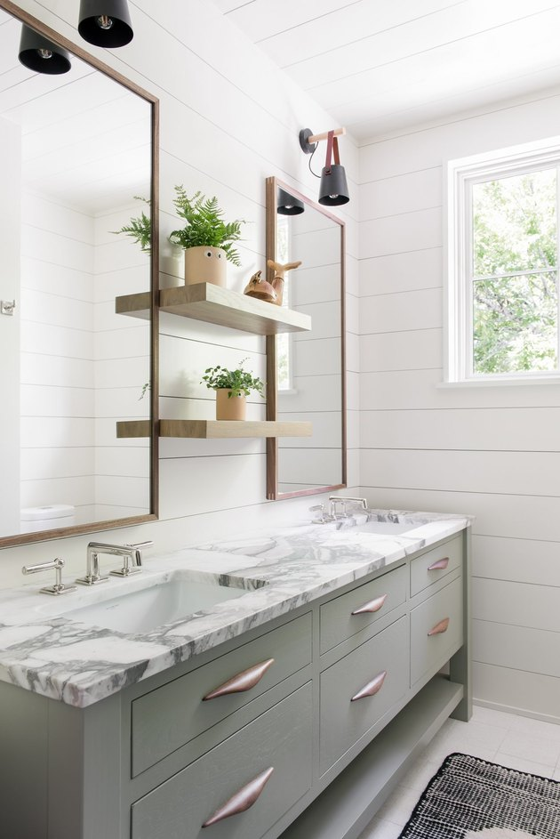 floating bathroom shelving with shiplap walls and marble countertop