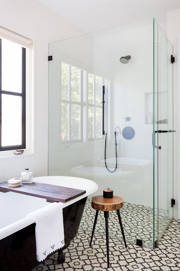 black and white bathroom with freestanding glass shower door and tub