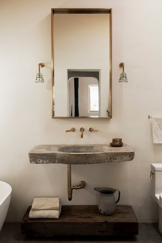 brass framed mirror and rustic bathroom shelving