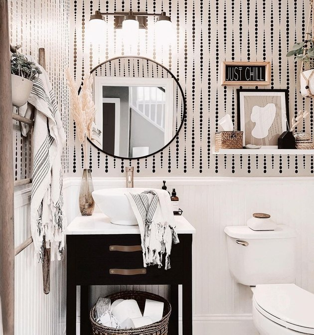 small modern bathroom with black and white wallpaper  and round mirror