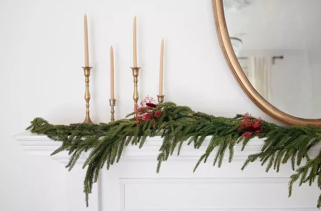 Dried floral garland on mantel with candles