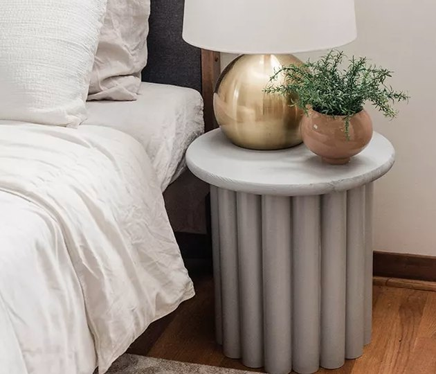 Ribbed side table with plant next to bed