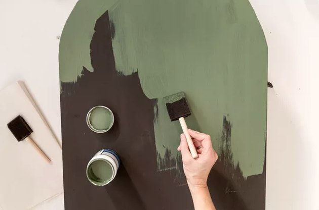 Painting green paint over black wood board