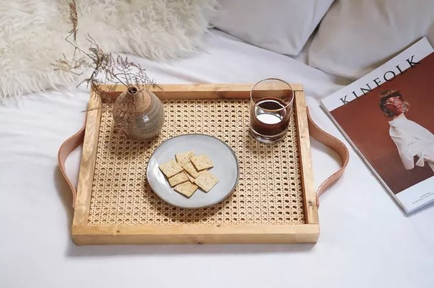 Cane and wood tray on bed