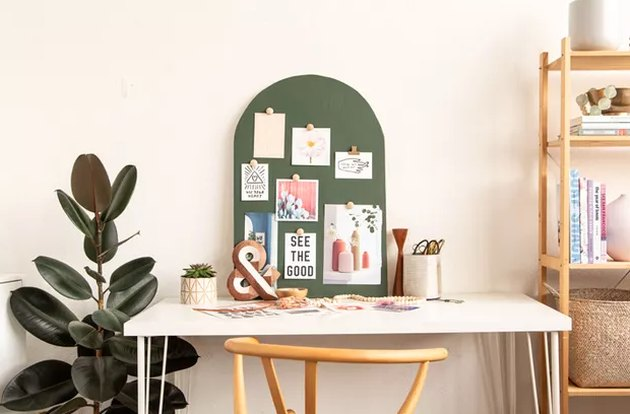 Green arched wood mood board on a desk