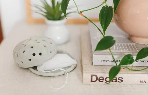 Air dry clay diffuser on cabinet with plants and books