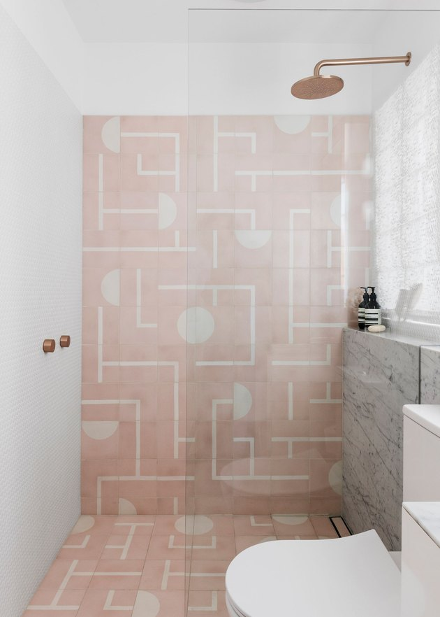 white bathroom with pink patterned tiles in the shower