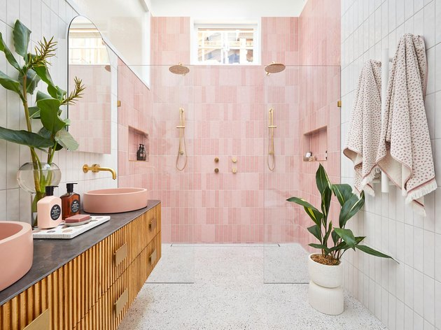 white bathroom with pink tiles in the shower and wooden vanity