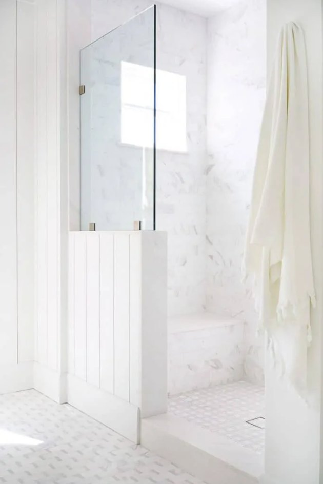 Coastal shower with glass, shiplap, and a white marble wall