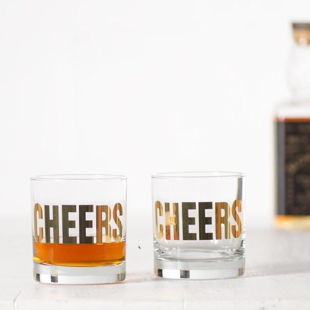 """two glasses with """"cheers"""" in gold and a bottle out of focus in the background"""