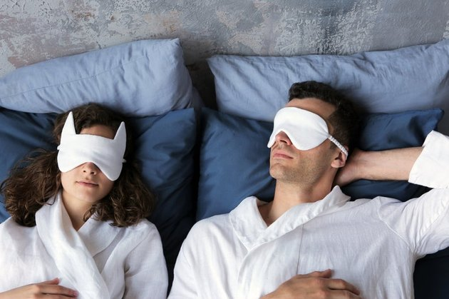 two people in bed wearing eye masks and bathrobes