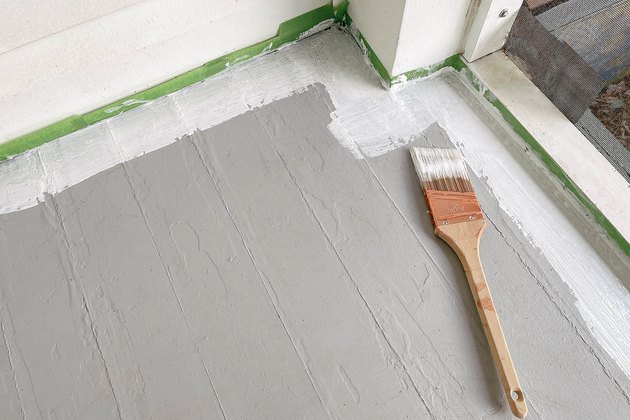 Painting primer along baseboards with paintbrush