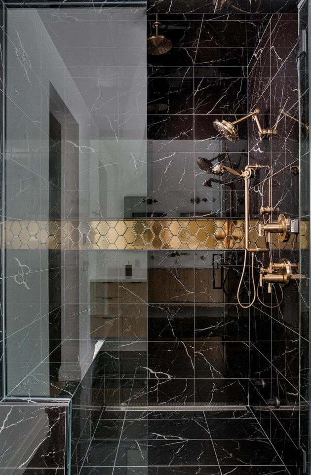elegant black tile shower with marble surround and gold finished fixtures