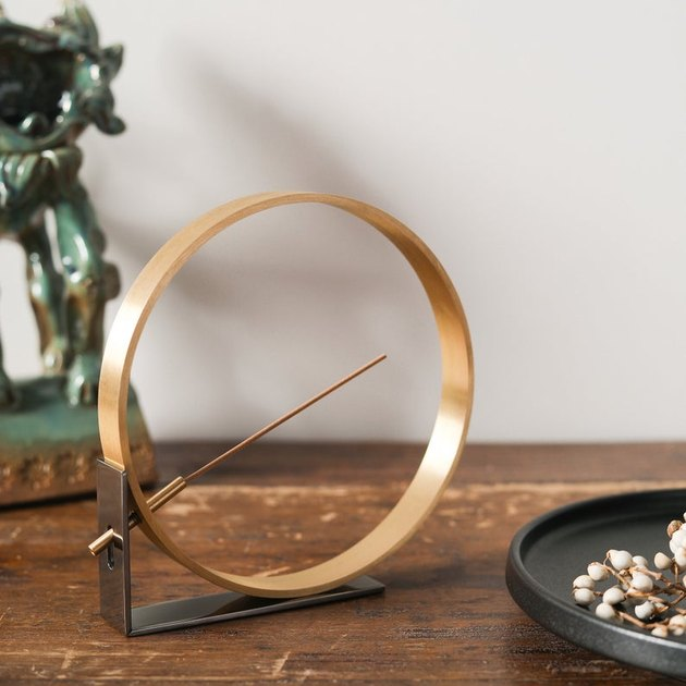 gold circular incense holder on wood table