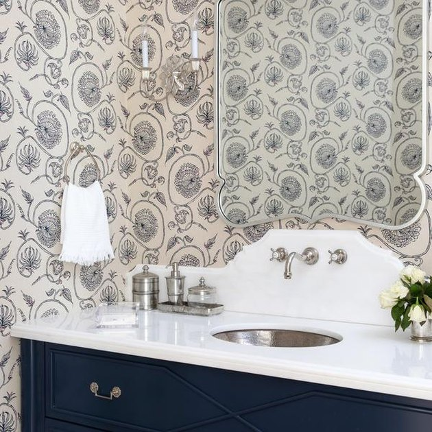 stainless steel bathroom sink in bathroom with wallpaper and ornate wall sconce