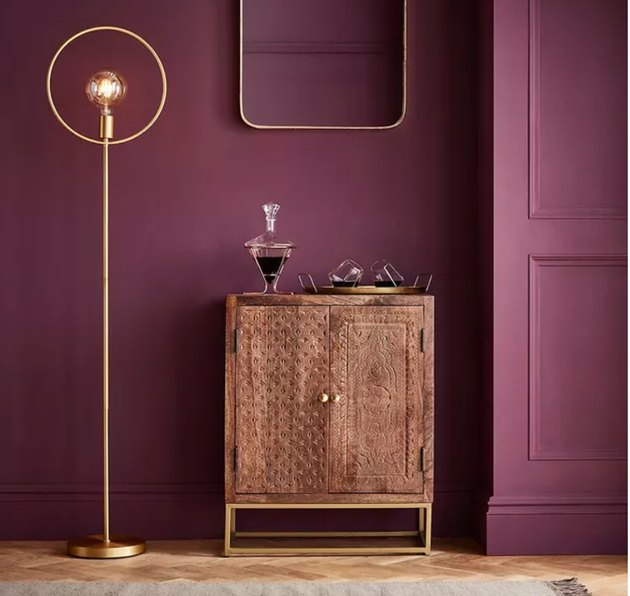 Graham & Brown epoch color of the year with bar cabinet and gold lamp