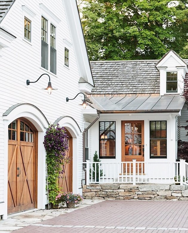 white house exterior with wood carriage style garage doors