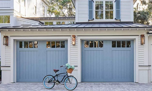 gray house exterior with blue carriage style garage doors