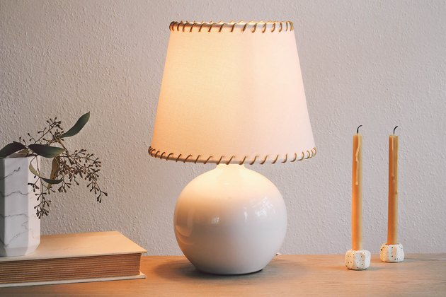 DIY whipstitched lampshade on desk with candles and vase