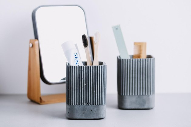 Gray textured concrete toothbrush holders alongside mirror