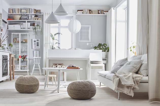 white living room space with shelves and couch