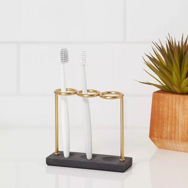 Gold and black toothbrush holder with white toothbrushes