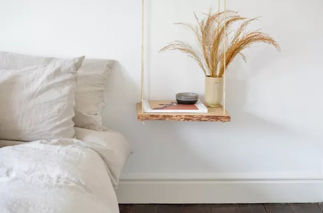 hanging wood nightstand next to bed