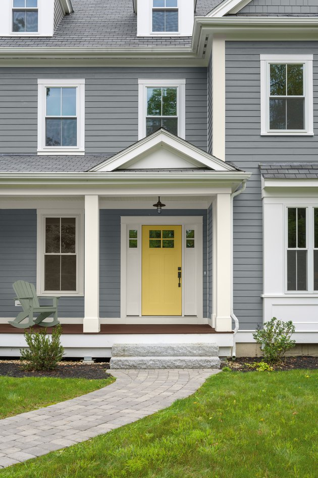 gray house exterior with yellow door
