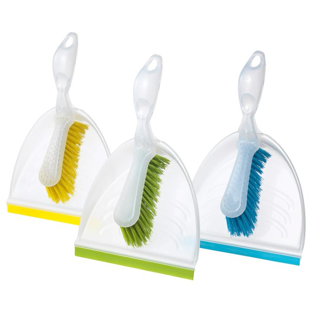 three dust pans and brushes in yellow, green, and blue