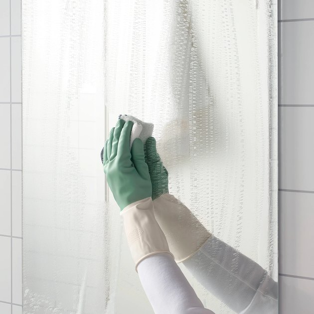 person with green gloves cleaning mirror