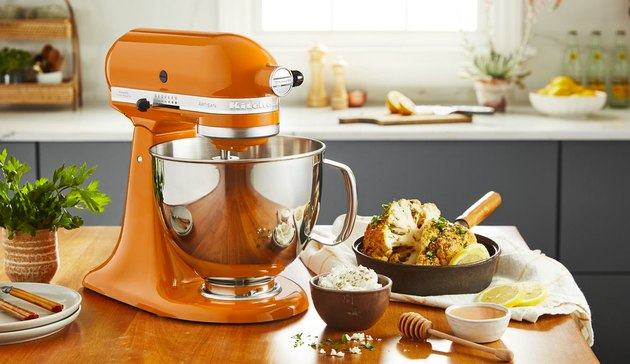 orange stand mixer on kitchen island with bowls nearby