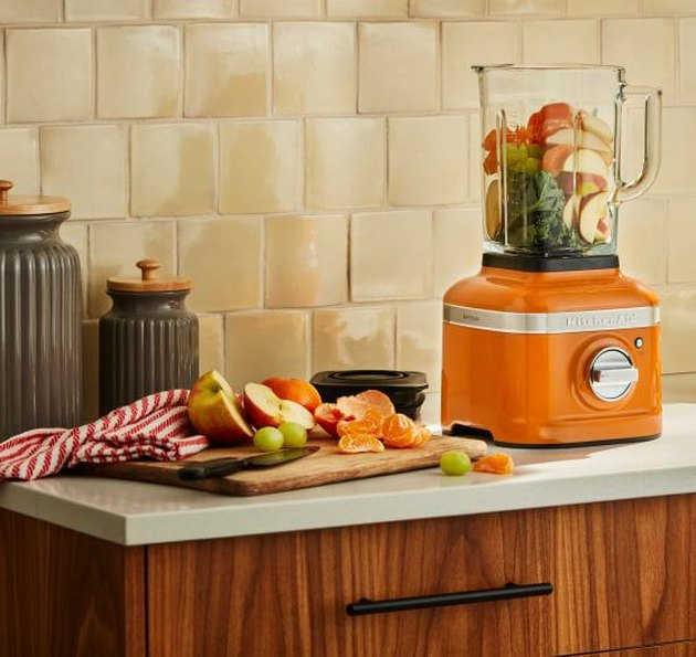 orange blender on countertop with fruit on cutting board nearby