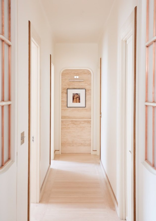 White Modern Hallway with light wood floors, art.