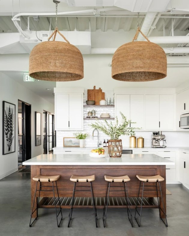 large woven rattan lights above white and wood island
