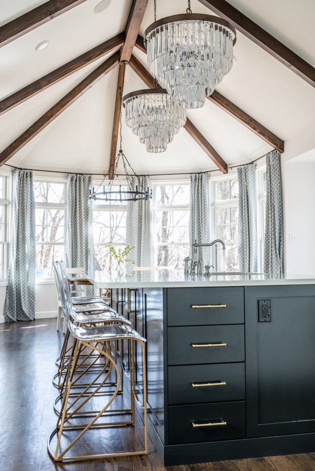 crystal chandeliers hanging above traditional black kitchen island