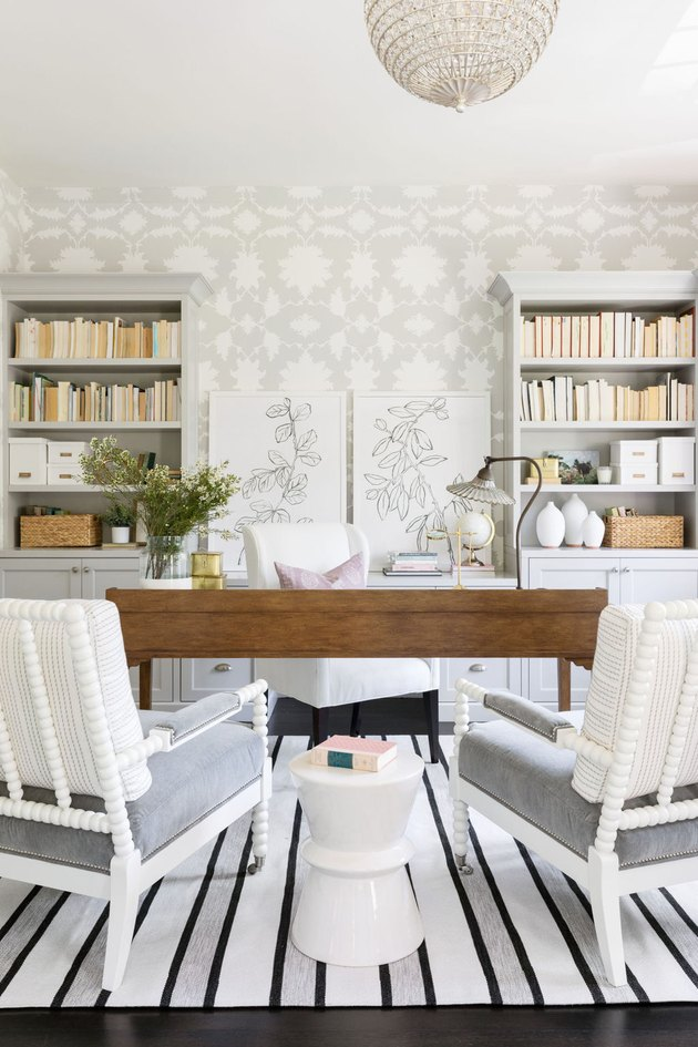gray home office with gray and white floral wallpaper and wood desk