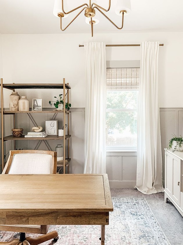 gray home office with gray wainscoting and brass chandelier