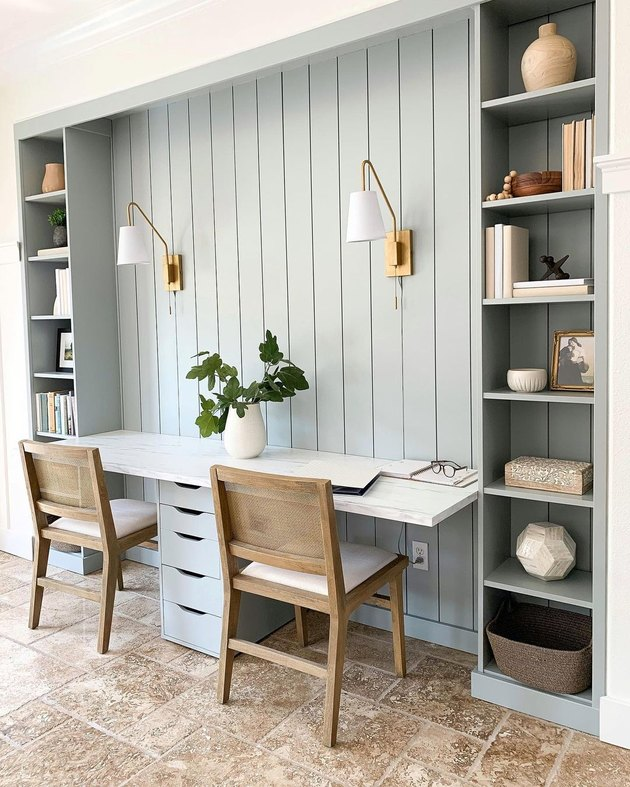 gray workspace with built-ins and brass wall sconces