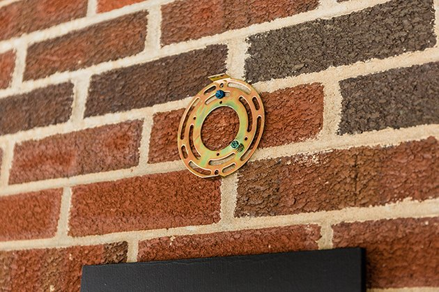 Install the hardware for the outdoor sconce on your porch wall.
