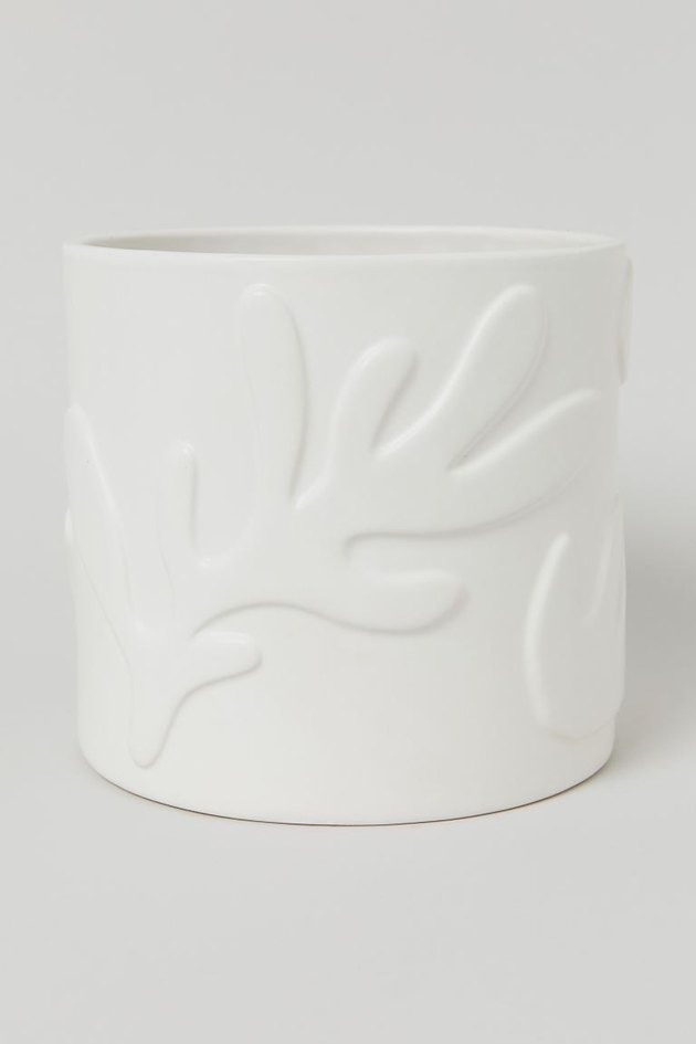 white stoneware plant pot with leaves