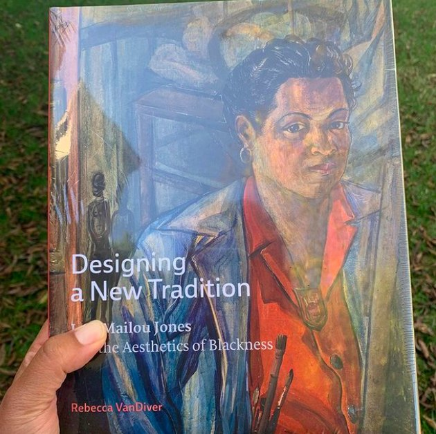 person holding book with title Designing a New Tradition
