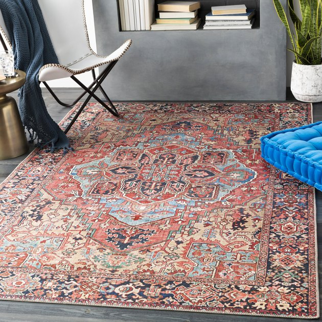 red and blue oriental rug in  modern room with concrete accents