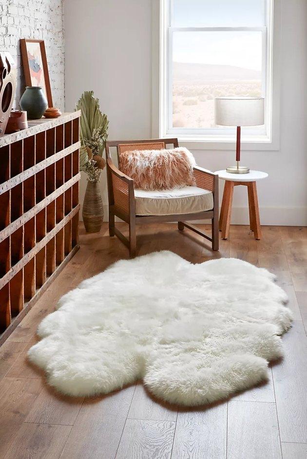 white plush sheepskin rug next to wooden shelf