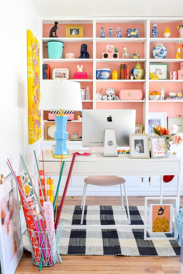 white home office with pink painted bookcase behind a white office desk, checkered rug