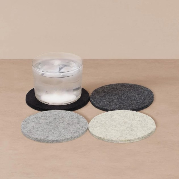 four wool coasters in muted colors, one with glass on top
