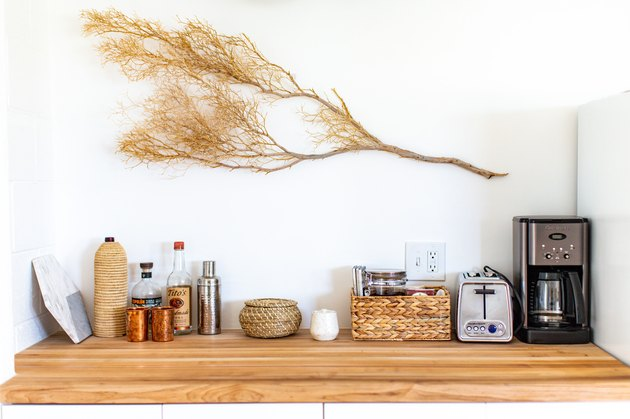 Butcher-Block countertop in kitchen with toaster and coffe maker on it and a branch hanging above it