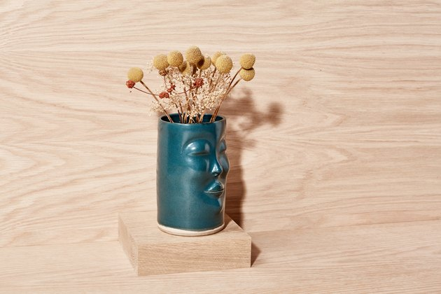 Green ceramic vase with dried billy buttons