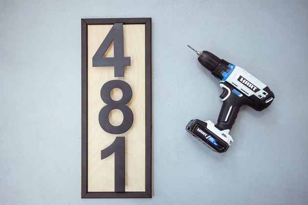 Modern black house numbers attached to wood board with power drill